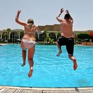 couple jumping in pool